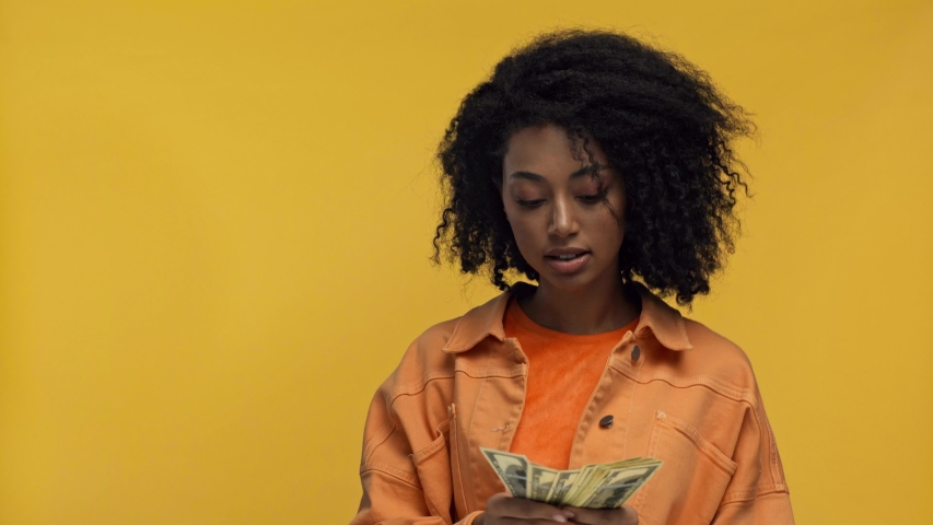 Smiling african american woman counting money isolated on yellow