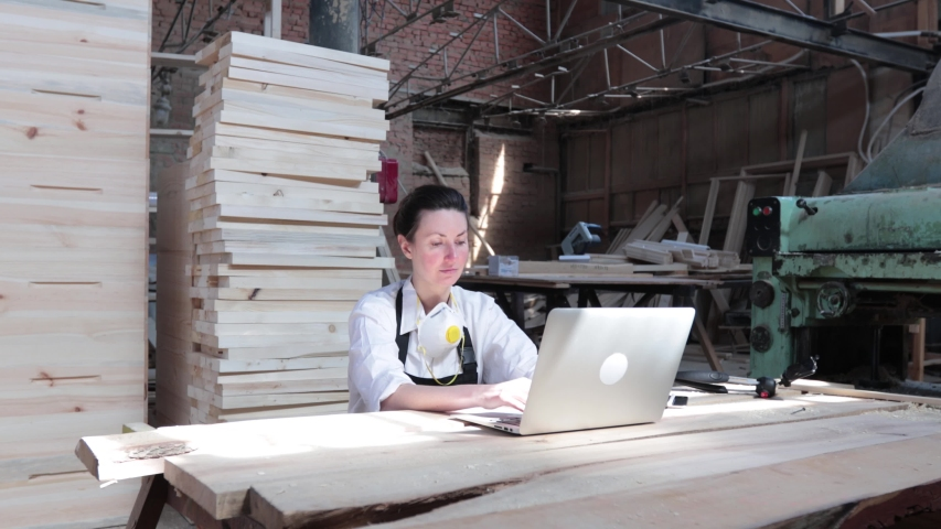 Woman working as carpenter in her own woodshop. She using a laptop and writes notes while being  in her workspace. Small business concept. | Shutterstock HD Video #1050200950