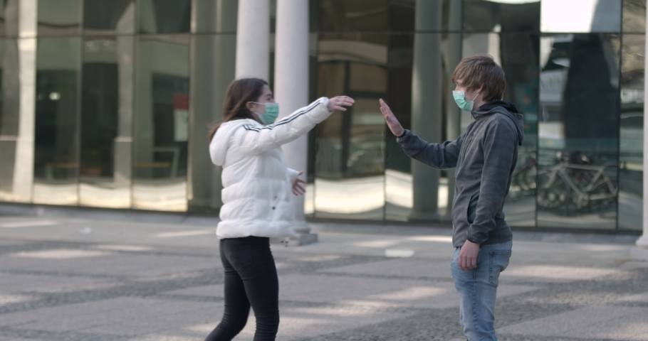 Social distancing - Young man stops his female friend to hug him due to coronavirus | Shutterstock HD Video #1050203479