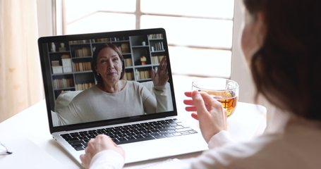 Young adult woman daughter or doctor video calling older mother patient on laptop computer screen. Two generations women talking by webcam. Videocall, family chat concept. Over shoulder close up view