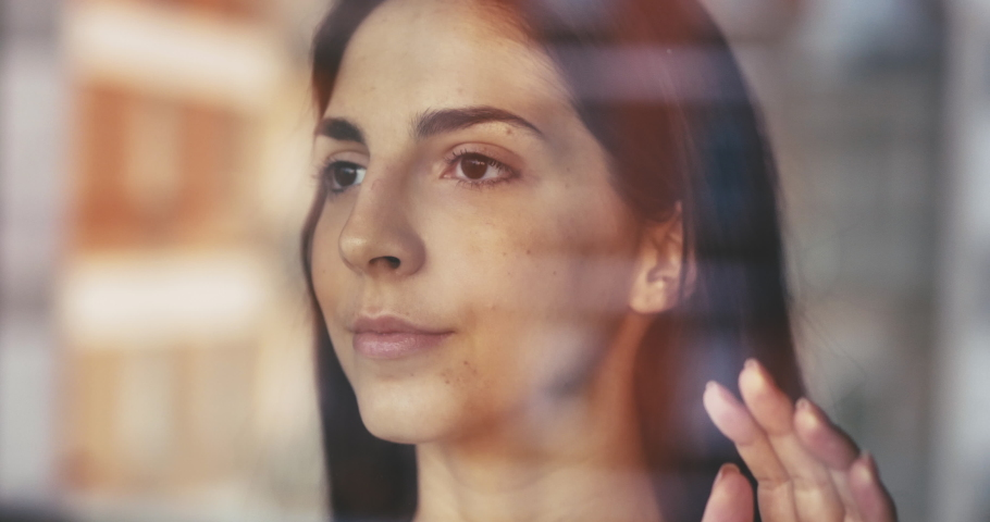 Authentic shot of a pensive young woman is touching a glass with her hand while looking through the window and smiling. Concept: life, dreams, hope, new beginning, environment, quarantine, covid-19 | Shutterstock HD Video #1050234025