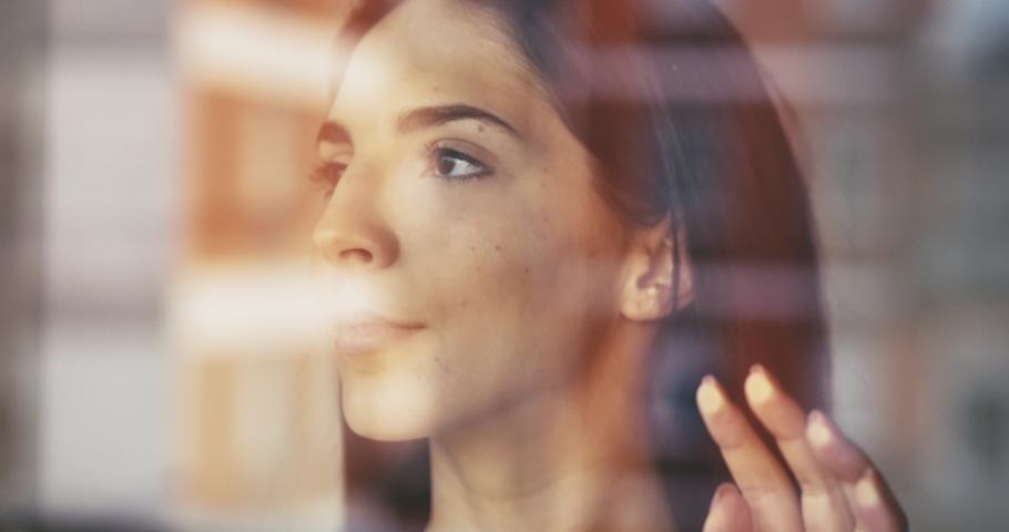 Authentic shot of a pensive young woman is touching a glass with her hand while looking through the window and smiling. Concept: life, dreams, hope, new beginning, environment, quarantine, covid-19 Royalty-Free Stock Footage #1050234025