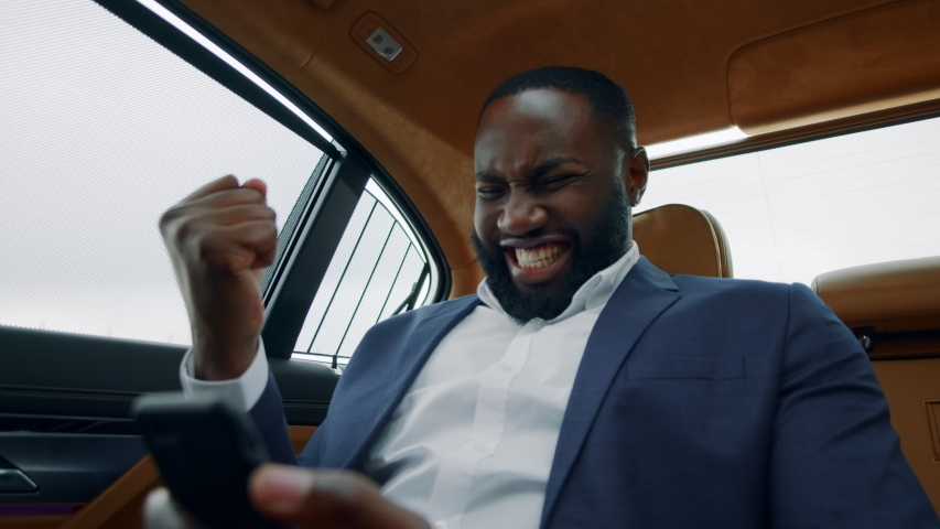 Portrait of winner african american man getting positive results on smartphone. Happy african businessman celebrating success at luxury car. Excited afro guy making yes gesture in vehicle.