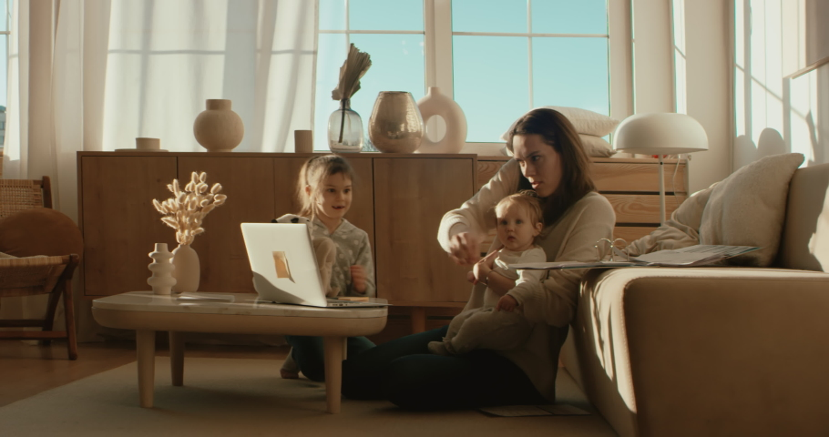 Mother working from home, having a phone call, while her daughters distract her and drawing attention. Shot on RED Dragon | Shutterstock HD Video #1050237946