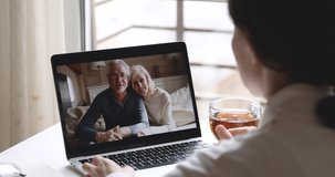 Over shoulder closeup view of young woman daughter video calling old senior parents talking with grandparents mom dad in webcam conference chat app on laptop screen on table. Family videocall concept.