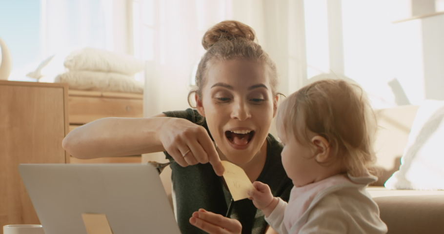 Mother working from home, feeding her daughter in front of laptop. Stay home, quarantine remote work. Shot on RED Dragon