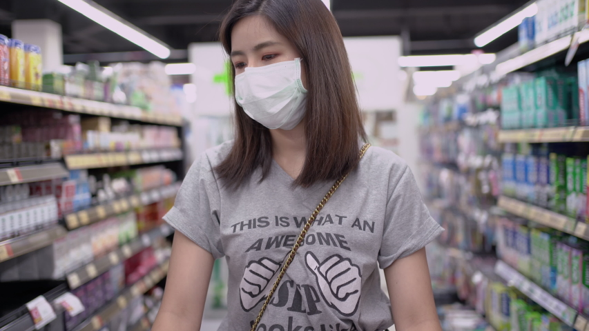 Young Asian woman in medical mask grocery walk toward camera shot, at supermarket during covid-19 coronavirus pandemic. Young lady stocks up food and toilet paper during quarantine and self-isolation | Shutterstock HD Video #1050248659