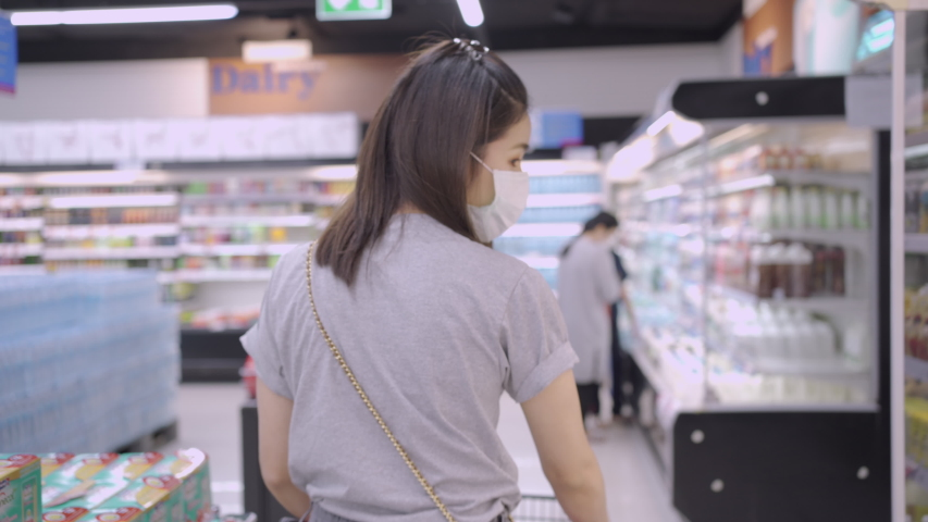 Young Asian lady wear mask walking with grocery cart, looking around at shelves and product, camera shot view from behind at supermarket during covid-19 corona virus pandemic. shopping list for dinner | Shutterstock HD Video #1050252721