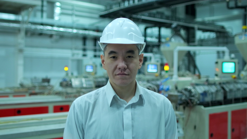 Portrait of Korean, chinese Asian professional architect engineer man businessman business people in hard hat looking at camera, engineering manufacture plant indoors, worker inspection, slow-mo 4 K | Shutterstock HD Video #1050253894
