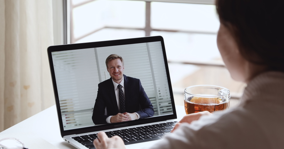 Smiling businessman boss wearing suit making video call conferencing with distance female worker, interviewing job applicant in home office webcam chat meeting on laptop screen. Over shoulder view Royalty-Free Stock Footage #1050257821