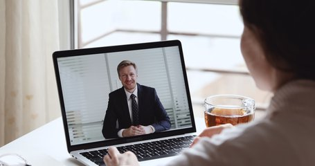 Smiling businessman boss wearing suit making video call conferencing with distance female worker, interviewing job applicant in home office webcam chat meeting on laptop screen. Over shoulder view