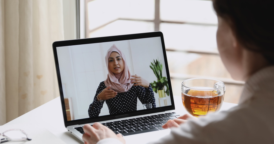 Young indian business woman wears hijab communicates with distance worker in webcam conference chat. Muslim online teacher make video call job interview. Elearning, over shoulder laptop screen view
