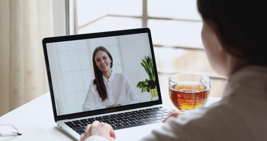 Online teacher and student, distance worker with manager or coach and client having distance chat video calling in app on laptop screen. Webcam job interview, training. Over shoulder closeup view Royalty-Free Stock Footage #1050257827