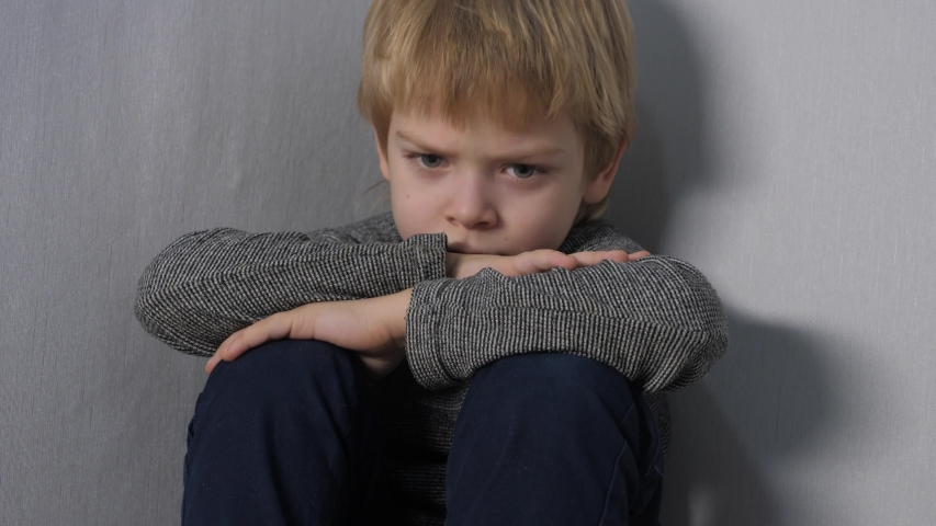 Domestic lifestyle violence concept . sad upset boy sitting in corner. Child punished sitting crying in the corner. Child abuse | Shutterstock HD Video #1050257842