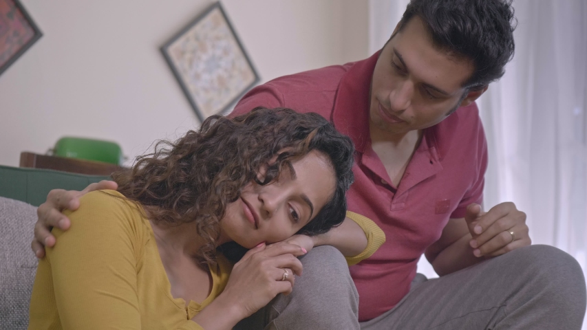 A sympathetic husband realises his wife is in distress/ sad/ stressed comforts/ consoles her without delay. A married couple in healthy/ loving relationship supports each other in the times of need. Royalty-Free Stock Footage #1050259171