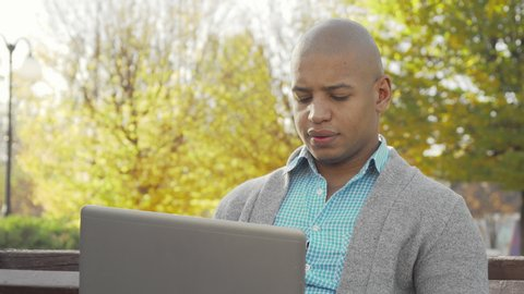 African American man working on laptop at local park in autumn