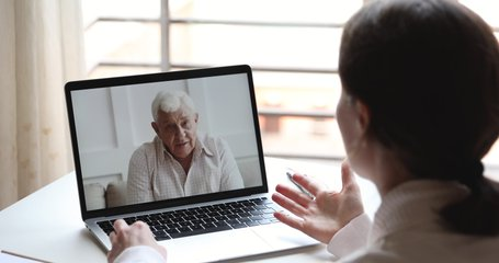 Happy elderly senior father video calling young daughter or doctor by webcam family chat. Grandfather enjoys virtual conversation conference videocall tech app concept. Over shoulder pc screen view