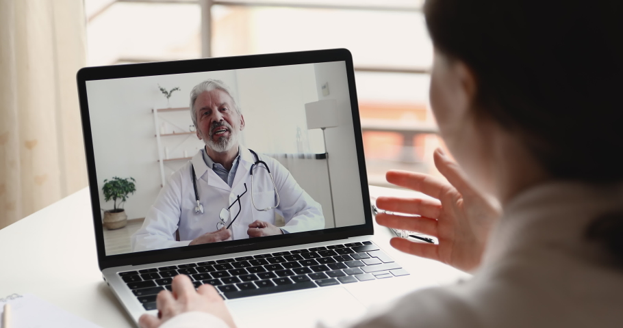 Senior male doctor videoconferencing woman remote patient consulting about corona virus pandemic during telemedicine video call in conference virtual webcam chat app. Over shoulder laptop screen view.
