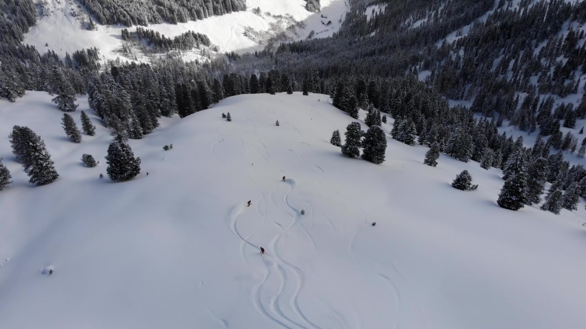 Drone following three snowboarders in action making beautiful turns on big backcountry mountain in Austria