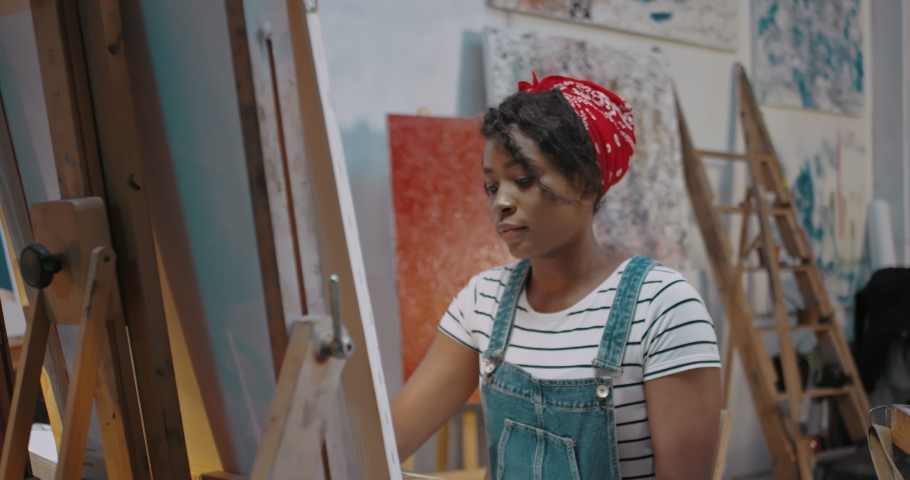 Young African American stylish female artist painting impressionism picture on canvas and creating artwork in art studio. Pretty girl student at fine art course. Beautiful woman studying at academy. Royalty-Free Stock Footage #1050303391