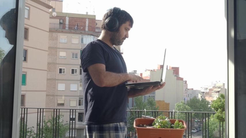 Man in pajamas with laptop making a video call with his family or friends from the balcony of his house. Concept: quarantine, confinement by Covid-19 | Shutterstock HD Video #1050311608