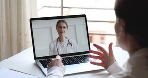 Telemedicine videoconference concept. Friendly female doctor consulting woman client patient by video call remote healthcare web cam app chat on laptop. Over shoulder closeup computer screen view