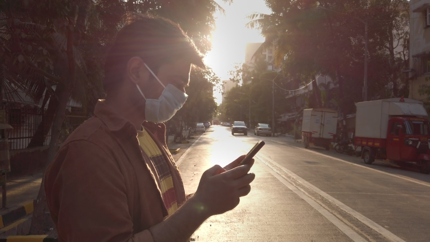 Coronavirus (Covid 19) Pandemic/ epidemic. A young man/ male/ guy wearing a protective mask on the city street/ road using mobile phone/ smartphone/ cellphone, Mumbai, India (April 2020)