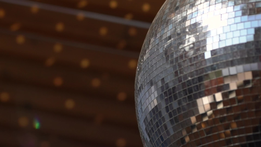 Disco ball for party spins on street, decor of courtyard, graduation, beginning of fun, casts glare from sunlight or bright lamp of the source of light on a wooden wall in the garden, home, club, home | Shutterstock HD Video #1050326344