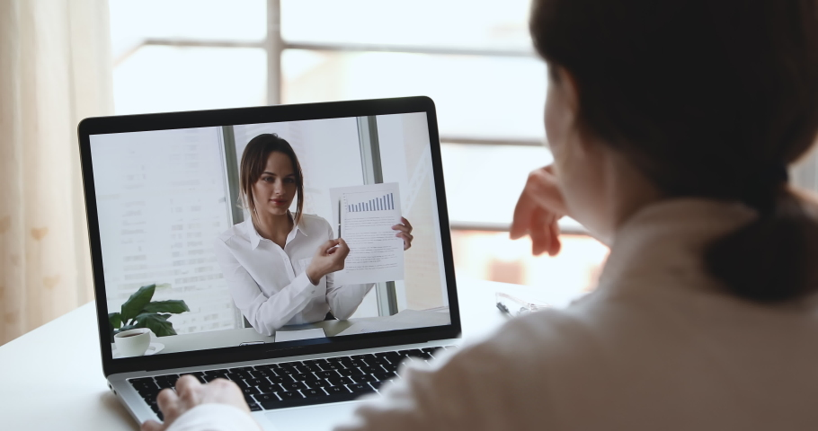 Businesswoman executive doing financial report presentation consulting distance client, remote worker, making video conference business call. Work from home webcam chat concept. Over shoulder view