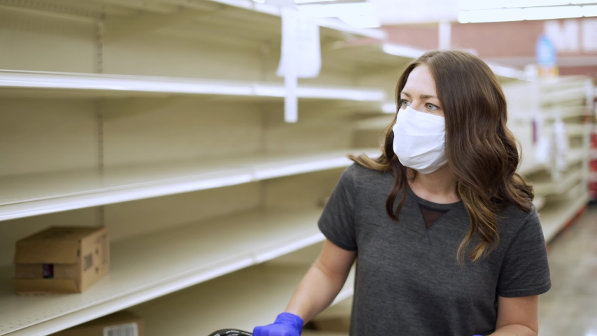 Woman shopping in grocery store for food while wearing PPE and preventing spread of virus germs by wearing face mask and looking at empty shelves. | Shutterstock HD Video #1050331951