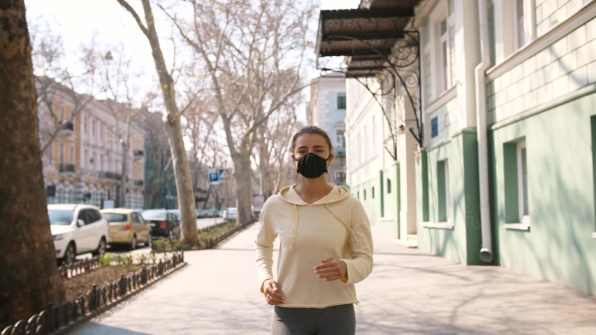 Portrait of young and fit woman running and jogging alone on the empty street in city center wearing protective face mask, slow motion | Shutterstock HD Video #1050332143