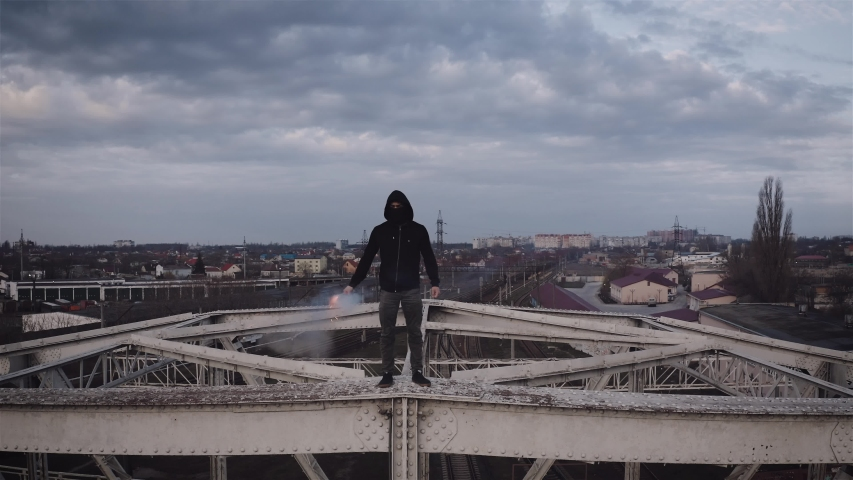Aerial view of young man in hoodie and balaclava standing on the top of the frame construction of an old steel frame bridge with red burning signal flare | Shutterstock HD Video #1050332146