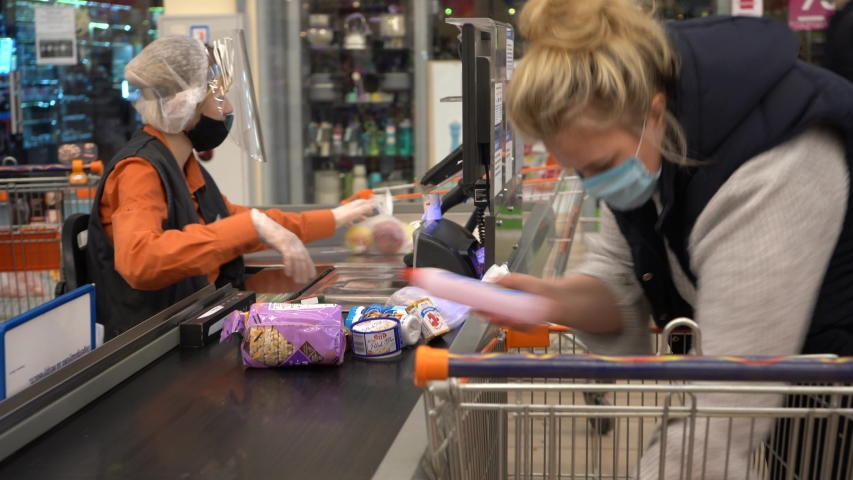 Europe, Kiev, Ukraine - April 2020: a buyer in a medical mask pays for products at the checkout in a supermarket during the Covid-19 coronavirus pandemic. Cash desk at the supermarket.