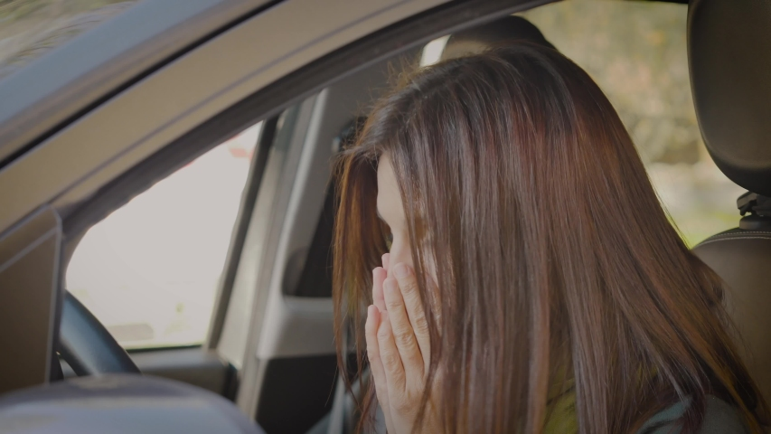 Ill adult woman sneezes without tissue inside car. Sick girl have allergic symptoms. Flu symptoms from cooling. Virus infection diffusion on car   Shutterstock HD Video #1050342595
