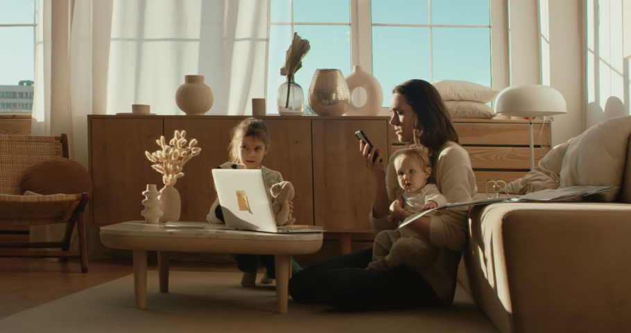 Mother working from home, making a work call surrounded by her daughters.. Shot on RED Dragon | Shutterstock HD Video #1050345730