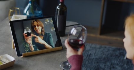 Attractive mid-30s Caucasian female clinking glasses while chatting with a friend or partner online in video chat, using a tablet