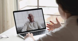 Video call talk with grandparent during social distancing quarantine concept. Young woman daughter granddaughter chatting with senior old father grandpa by web cam on laptop screen. Over shoulder view