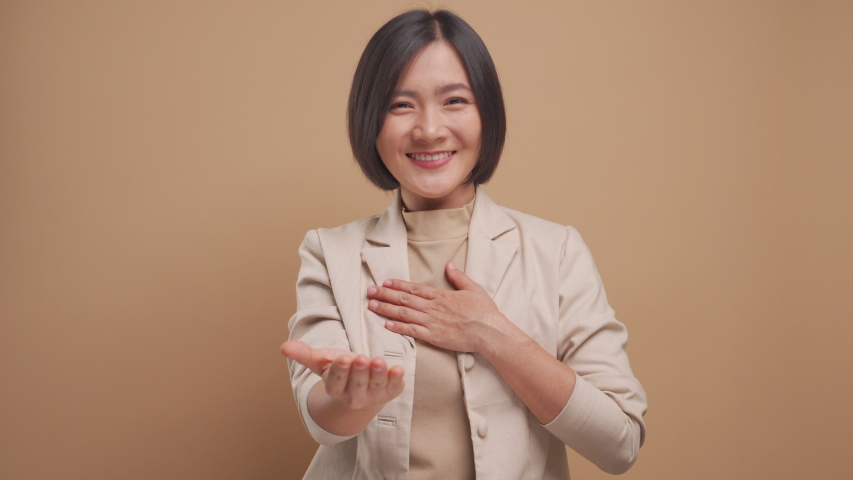 Asian business woman looking at camera happy smiling and say thank you by sign language isolated over beige background. 4K video Royalty-Free Stock Footage #1050354424