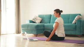 Attractive young woman doing yoga stretching yoga online at home. Self-isolation is beneficial, entertainment and education on the Internet. Healthy lifestyle concept.