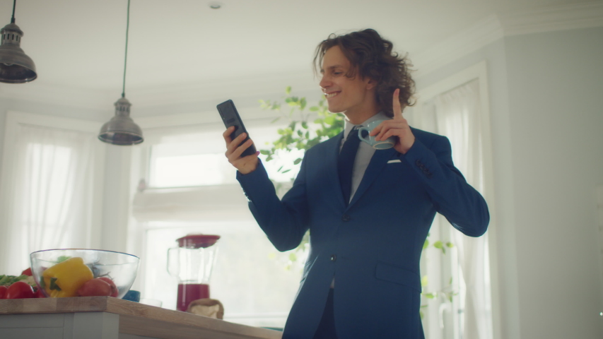 Happy Young Man with Long Hair Dancing at Home while Wearing Blue Business Suit. He is Listening to Music on a Mobile. Energetic Man Using Smartphone in a Kitchen with Healthy Vegetables.