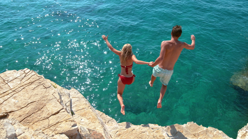 SLOW MOTION: Joyful tourist couple decides to jump off a rocky cliff and dive into sea. Unrecognizable man holds his girlfriend's hand while diving into the deep blue sea on a sunny summer day.