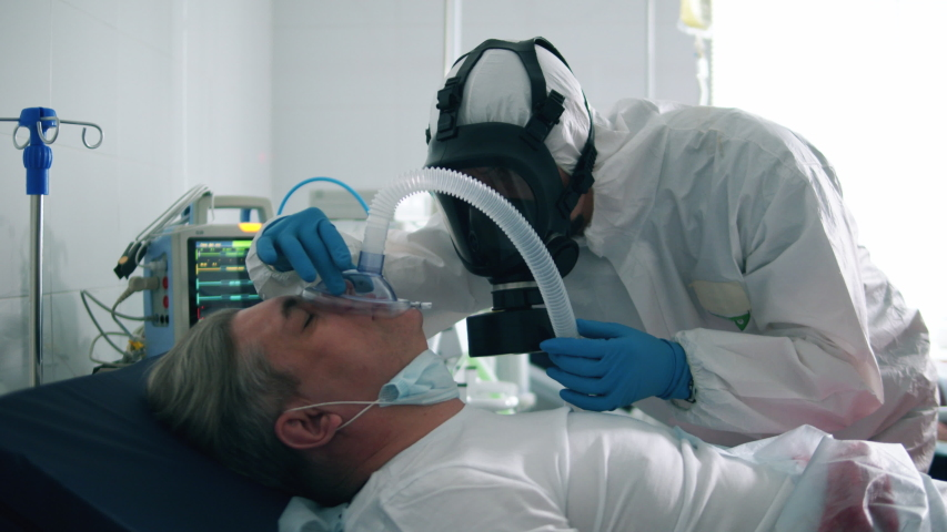 Paramedic is putting an oxygen mask on a male patient. Coronavirus, covid-19 infected patients in a clinic. Royalty-Free Stock Footage #1050382978