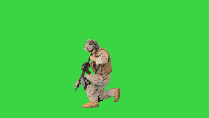 Soldier walking aiming with rifle and using radio on a Green Screen, Chroma Key. | Shutterstock HD Video #1050383458