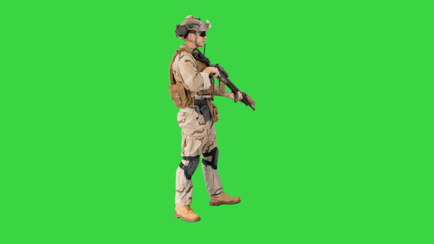 Soldier sits down for aiming and shooting with rifle on a Green Screen, Chroma Key. | Shutterstock HD Video #1050383512