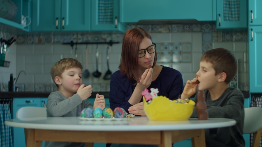 30s mother with two sons eating Easter chocolate bunnies at home on blue kitchen. Happy family celebrating Easter with colored eggs and chocolate bunnies.  | Shutterstock HD Video #1050383956