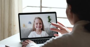 Female tutor video calling teaching cute preschool kid girl using remote learning app talking with happy child in chat on laptop screen. Home conference children education. Over shoulder closeup view