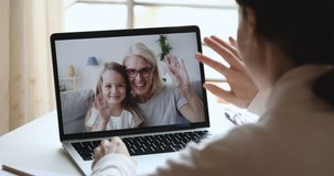 Young woman mom, doctor or tutor video calling chatting by web cam app with happy cute child daughter and old grandma babysitter on laptop screen. Family videocall concept. Over shoulder closeup view