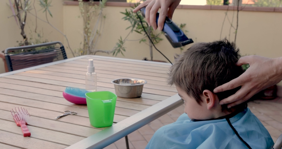 Mother cutting the hair of a little son with a hair clipper on the terrace of his home during the coronavirus quarantine in Lombardy, Italy | Shutterstock HD Video #1050388987