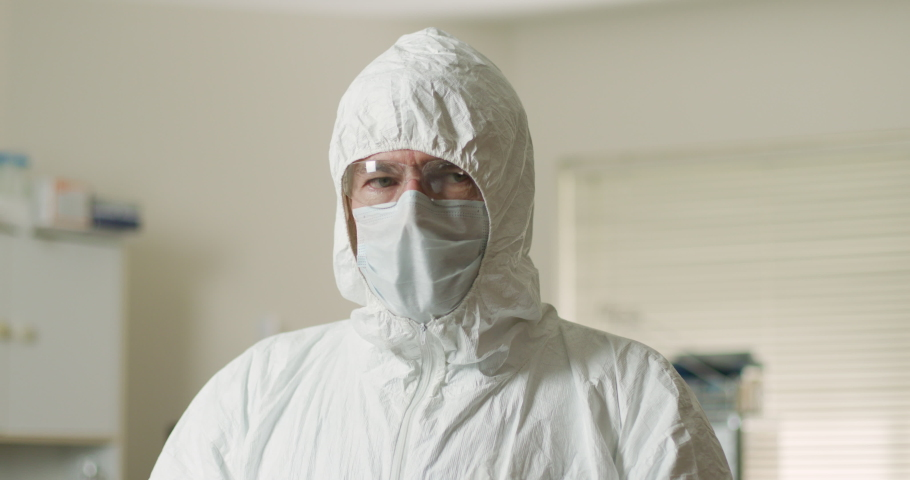 A tired doctor or healthcare employee removes his PPE after a long shift dealing with contagious patients dealing with or exposed to the coronavirus.   Shutterstock HD Video #1050390175