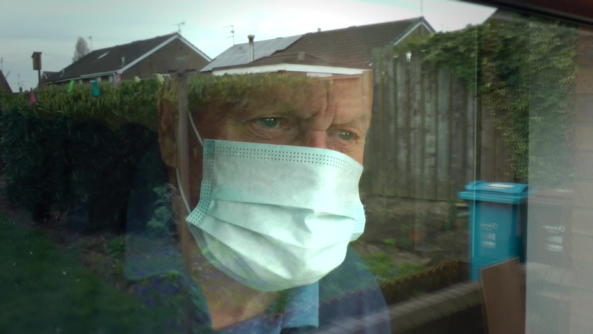 UK lockdown. Coronavirus. Old man wearing face mask, PPE. Looks out of nursing, care home window. Social distancing, self isolation, stay at home, Covid 19. Yorkshire, England UK. 12/04/2020